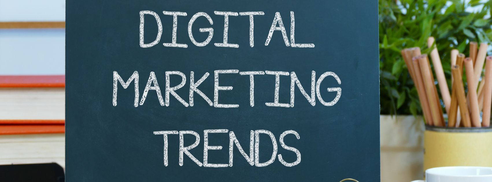 digital marketing trends - message text on a blackboard with pencils coffee cup and mobile phone.