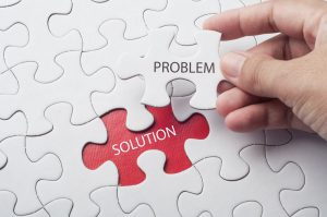 Hand holding piece of jigsaw puzzle with word problem & solution.